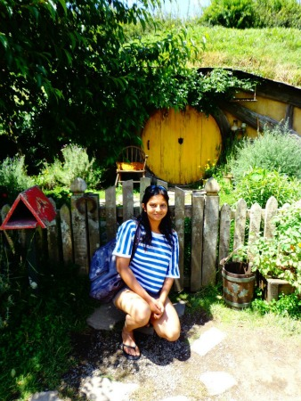 Sonal outside a hobbit hole at Hobbiton, NZ